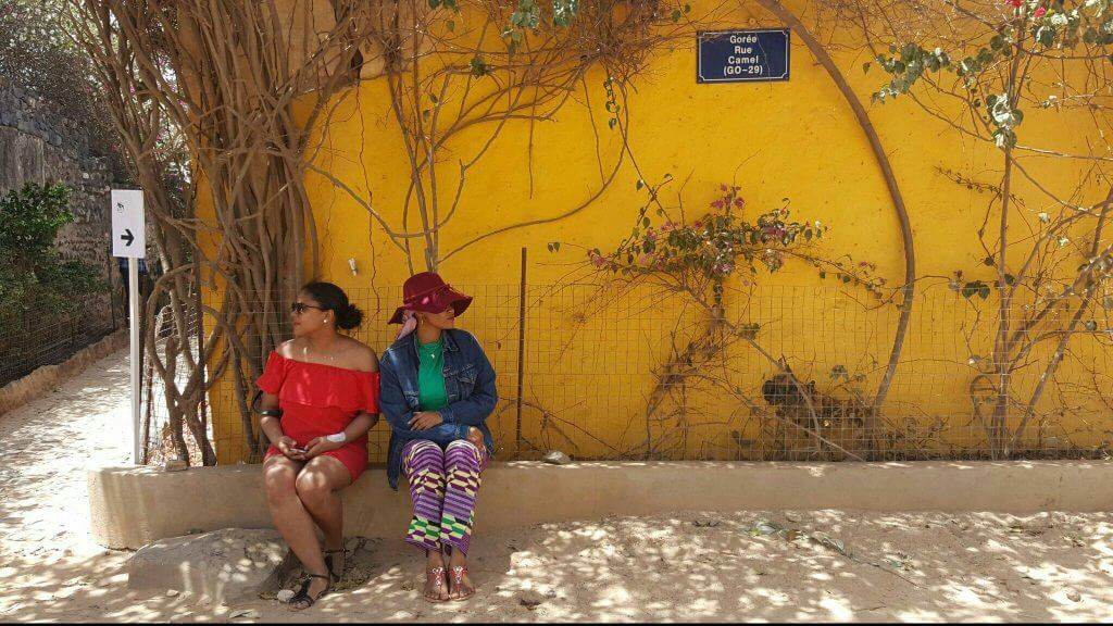 we-sisterhood-dakar-36-goree-femmes-noires-mur-jaune-regard